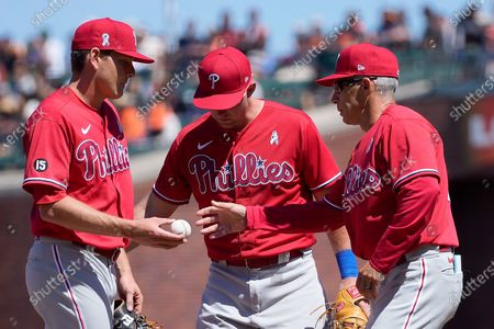 Philadelphia Phillies pitcher Spencer Howard, left, hands the ball to manager Joe Girardi, right, as he is taken out of a baseball game during the seventh inning against the San Francisco Giants, in San Francisco