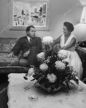 Richard M. Nixon (L) sitting with Mrs. Norman Chandler (R) on the couch.