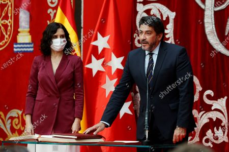 Madrid's regional Transport and Infrastructure Minister David Perez Garcia (R), next to Madrid's regional President Isabel Diaz Ayuso (L), during the regional Ministers' swear-in ceremony in Madrid, Spain, 21 June 2021. Ayuso won regional snap elections held 04 May 2021.