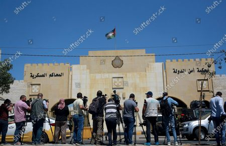 Reporters stand outside the state security court where the trial of Bassem Awadallah, a former royal adviser, and Sharif Hassan bin Zaid, a distant cousin of the king, is taking place, in Amman, Jordan, . Awadallah, who has Jordanian, U.S. and Saudi citizenship, and bin Zaid, pleaded not guilty Monday to sedition and incitement charges, a defense lawyer said. The defendants are accused of conspiring with a senior royal - Prince Hamzah, a half-brother of the king - to foment unrest against the monarch while soliciting foreign help