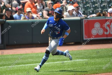Toronto Blue Jays Bo Bichette scores a run on double hit by Teoscar Hernandez against Baltimore Orioles starting pitcher Matt Harvey during the fifth inning of a baseball game, in Baltimore