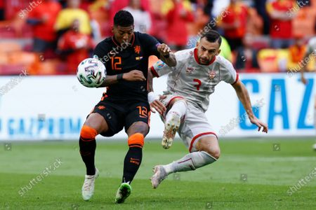 Patrick van Aanholt of the Netherlands, left, and North Macedonia's Ivan Trichkovski vie for the ball during the Euro 2020 soccer championship group F match between North Macedonia and Netherlands, at the Johan Cruyff ArenA in Amsterdam, Netherlands