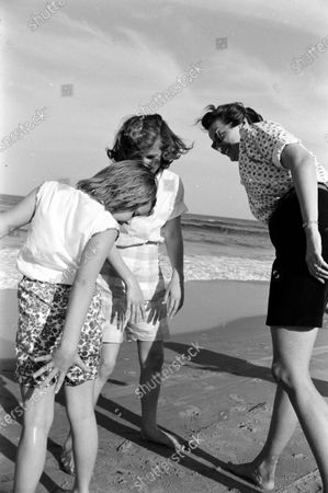 Louise Brewer Shepard, wife of astronaut Alan B. Shepard, Jr., checking on her daughters, 11-year-old Laura and 8-year-old Julie, who have been playing in the waves on the beach near their home in Virginia Beach, Virginia, April 1959.