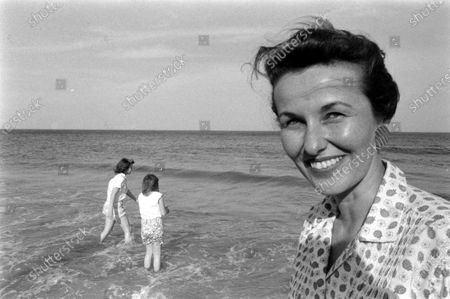 Louise Brewer Shepard, wife of astronaut Alan B. Shepard, Jr., smiling at the camera while her daughters, 11-year-old Laura and 8-year-old Julie, play in the waves on the beach near their home in Virginia Beach, Virginia, April 1959.