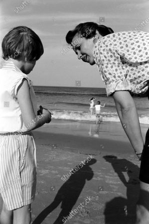 Louise Brewer Shepard, wife of astronaut Alan B. Shepard, Jr., talking with her niece, 7-year-old Alice Williams, while her daughters, 11-year-old Laura and 8-year-old Julie, play in the waves on the beach near their home in Virginia Beach, Virginia, April 1959.