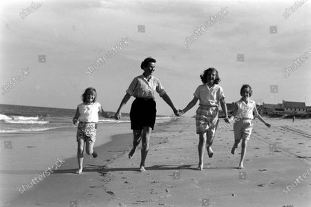 Louise Brewer Shepard, wife of astronaut Alan B. Shepard, Jr., with their daughters, 11-year-old Laura and 8-year-old Julie, and 7-year-old niece, Alice Williams, who lives permanently with them, playing on the beach near their home in Virginia Beach, Virginia, April 1959.