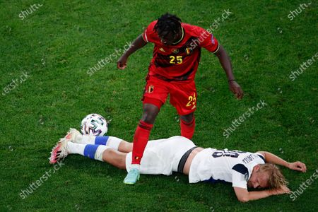 Belgium's Jeremy Doku, top, fights for the ball with Finland's Joel Pohjanpalo during the Euro 2020 soccer championship group B match between Finland and Belgium at Saint Petersburg Stadium in St. Petersburg, Russia