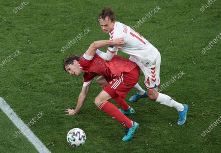 Russia's Mario Fernandes, left, and Denmark's Mikkel Damsgaard challenge for the ball during the Euro 2020 soccer championship group B match between Russia and Denmark at the Parken stadium in Copenhagen, Denmark