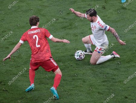 Russia's Mario Fernandes, left, and Denmark's Pierre-Emile Hojbjerg challenge for the ball during the Euro 2020 soccer championship group B match between Russia and Denmark at the Parken stadium in Copenhagen, Denmark