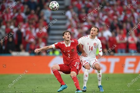 Russia's Mario Fernandes, left, is challenged by Denmark's Mikkel Damsgaard during the Euro 2020 soccer championship group B match between Russia and Denmark at the Parken stadium in Copenhagen, Denmark