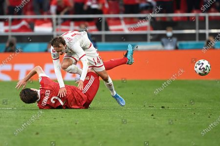 Denmark's Mikkel Damsgaard, top, is tackled by Russia's Mario Fernandes during the Euro 2020 soccer championship group B match between Russia and Denmark at the Parken stadium in Copenhagen, Denmark