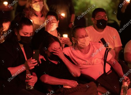 """Dora Molina Mejia with her daughters Karla Acosta, left, and Jenny Acosta, right, attend a vigil for her husband Tomas """"Jose"""" Mejia at SEIU United Service Workers West headquarters near downtown Los Angeles on Thursday, June 17, 2021. Mejia was a worker at Park La Brea who was stabbed to death. (Myung J. Chun / Los Angeles Times)"""