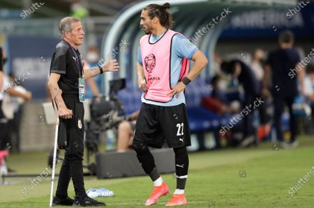 Stock Picture of Uruguay's Oscar Tabarez, left, talks to his player Martin Caceres during a Copa America soccer match at Arena Pantanal stadium in Cuiaba, Brazil