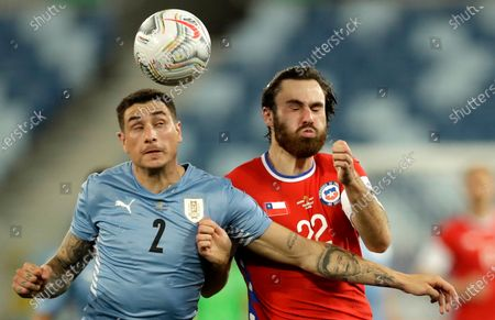 Uruguay's Jose Gimenez, left, and Chile's Ben Brereton battle for the ball during a Copa America soccer match at Arena Pantanal stadium in Cuiaba, Brazil