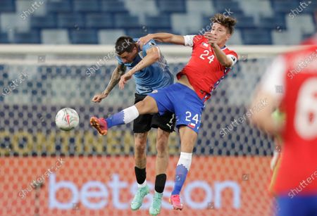 Chile's Luciano Arriagada, right, and Uruguay's Jose Gimenez battle for the ball during a Copa America soccer match at Arena Pantanal stadium in Cuiaba, Brazil