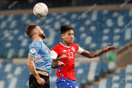 Uruguay's Nahitan Nandez, left, and Chile's Erick Pulgar battle for the ball during a Copa America soccer match at Arena Pantanal stadium in Cuiaba, Brazil