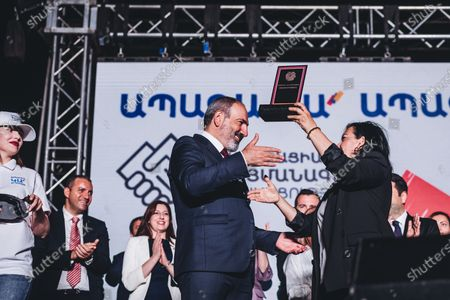 Nikol Pashinyan receives a plaque during the celebration of his victory in the Armenian parliamentary elections in Yerevan's Republic Square.