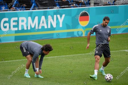 Germany's Emre Can, right, kicks the ball while Leroy Sane adjusts his shoe during a training session of the German national soccer team in Herzogenaurach, Germany, . Germany will face Hungary for a Euro 2020 Group F soccer match on Wednesday, June 23, 2021