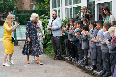 Camilla Duchess of Cornwall, Patron of BookTrust, is greeted by schooldchildren during her visit to Griffin Primary School in Nine Elms, London, with Waterstones Children's Laureate, Cressida Cowell (left) to open the new 'Life-changing Library'.