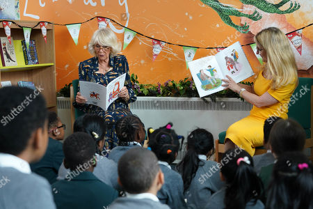 Camilla Duchess of Cornwall, Patron of BookTrust, reading to schoolchildren during her visit to Griffin Primary School, Nine Elms, London, with Waterstones Children's Laureate, Cressida Cowell (right) to open the new 'Life-changing Library'.