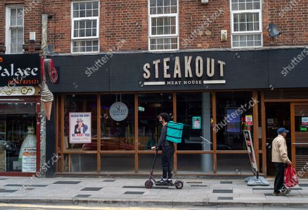 The popular trend of having take away food continues. A young man heads out on an e-scooter for Deliveroo. Due to the spread of the Covid-19 Indian Variant surge testing is taking place across Slough