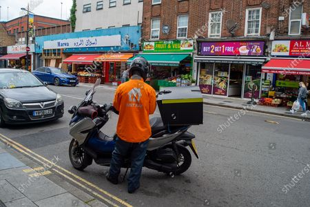 A Just East moped driver ready to make a delivery. Due to the spread of the Covid-19 Indian Variant surge testing is taking place across Slough