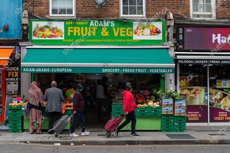 Shoppers walk past a Fruit and Veg shop in Slough High Street. Due to the spread of the Covid-19 Indian Variant surge testing is taking place across Slough