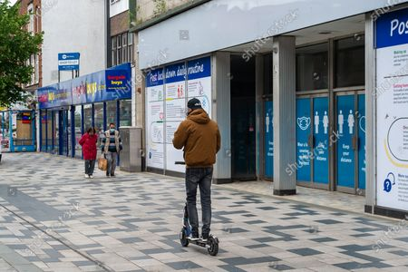 A young man rides his e-scooter through a pedestrian area in Slough High Street. Confusion remains about where e-scooters can be used