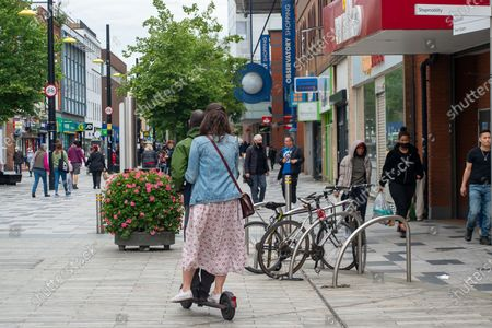 A man and a lady ride an e-scooter through a pedestrian area in Slough High Street. The use of private e-scooters has become popular during the Covid-19 lockdown