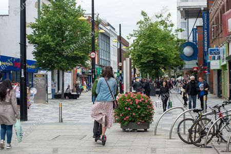 Stock Picture of A man and a lady ride an e-scooter through a pedestrian area in Slough High Street. The use of private e-scooters has become popular during the Covid-19 lockdown
