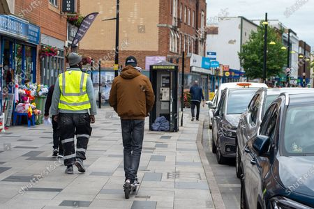 Stock Image of A young man rides his e-scooter through a pedestrian area in Slough High Street. Confusion remains about where e-scooters can be used