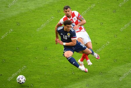 Scotland's Che Adams and Croatia's Dejan Lovren challenge for the ball during the Euro 2020 soccer championship group D match between Scotland and Croatia at the Hampden Park Stadium in Glasgow