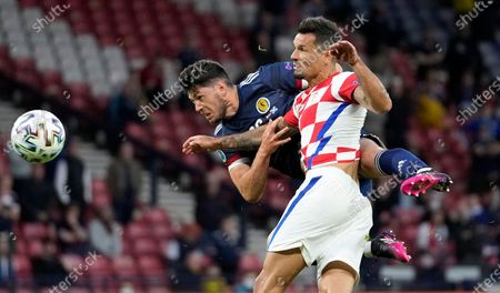 Croatia's Dejan Lovren and Scotland's Scott McKenna challenge for the ball during the Euro 2020 soccer championship group D match between Croatia and Scotland at the Hampden Park Stadium in Glasgow