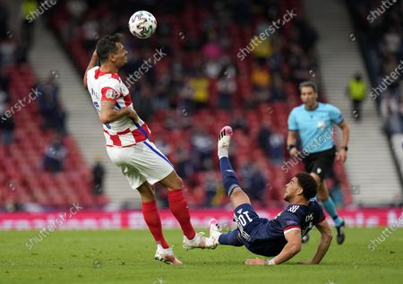 Croatia's Dejan Lovren, left, and Scotland's Che Adams challenge for the ball during the Euro 2020 soccer championship group D match between Croatia and Scotland at the Hampden Park Stadium in Glasgow