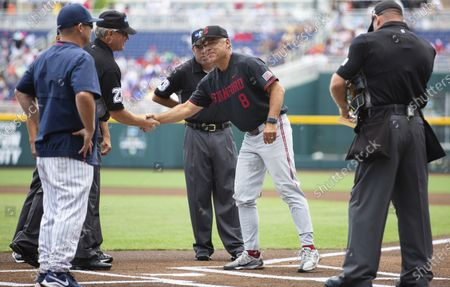 Stanford head coach David Esquer, right, shakes hands with an umpire while meeting with Arizona head coach Jay Johnson before their baseball game in the College World Series, at TD Ameritrade Park in Omaha, Neb