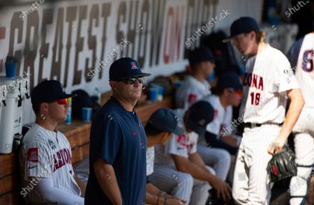 Arizona head coach Jay Johnson watches from the dugout as Stanford celebrates their 14-5 victory during a baseball game in the College World Series, at TD Ameritrade Park in Omaha, Neb