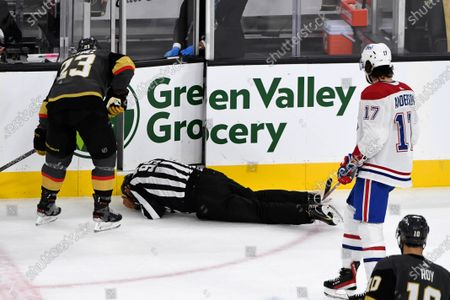 Linesman Jonny Murray (95) falls to the ice after being hit as Vegas Golden Knights defenseman Alec Martinez (23) and Montreal Canadiens right wing Josh Anderson (17) skate towards him during the first period in Game 5 of an NHL hockey Stanley Cup semifinal playoff series against the Montreal Canadiens, in Las Vegas
