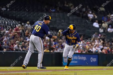 Milwaukee Brewers' Kolten Wong (16) celebrates his home run against the Arizona Diamondbacks with Brewers third base coach Jason Lane (40) during the first inning of a baseball game, in Phoenix