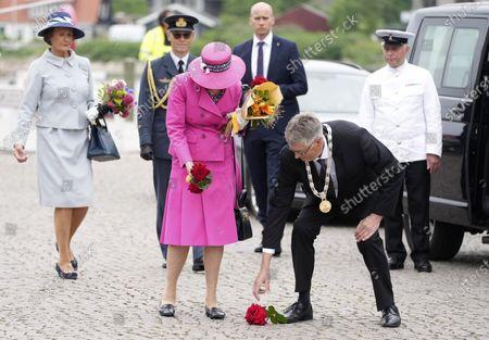 Queen Margrethe II of Denmark (C) arrives at Soenderborg Harbor with the Royal Yacht Dannebrog, in Soenderborg, Denmark, 23 June 2021. Mayor Erik Lauritzen (C-R) picks up flowers that the Queen loses.