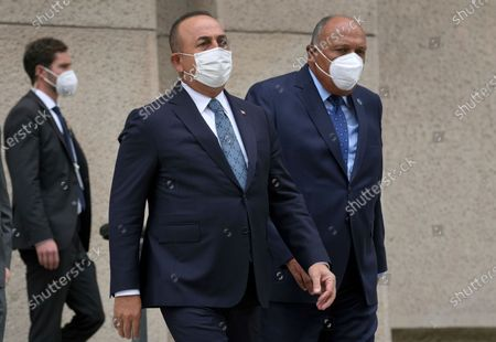 Turkey's Foreign Minister Mevlut Cavusoglu, left, and his counterpart from Egypt, Sameh Shoukry, right, arrive for a group photo during the 'Second Berlin Conference on Libya' at the foreign office in Berlin, Germany