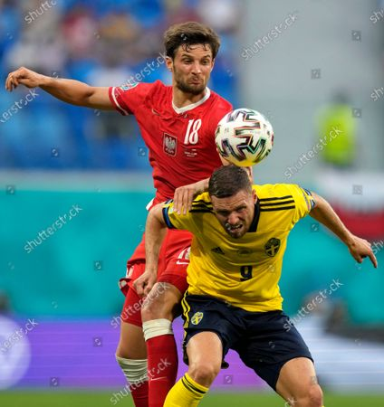Poland's Bartosz Bereszynski, left, challenges Sweden's Marcus Berg during the Euro 2020 soccer championship group B match between Sweden and Poland at Saint Petersburg stadium in St. Petersburg, Russia