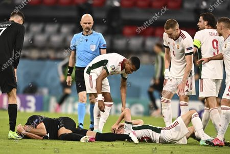 Stock Image of Germany's Ilkay Gundogan, left, and Hungary's Andras Schaefer lie injured on the pitch during the Euro 2020 soccer championship group F match between Germany and Hungary at the Allianz Arena in Munich, Germany
