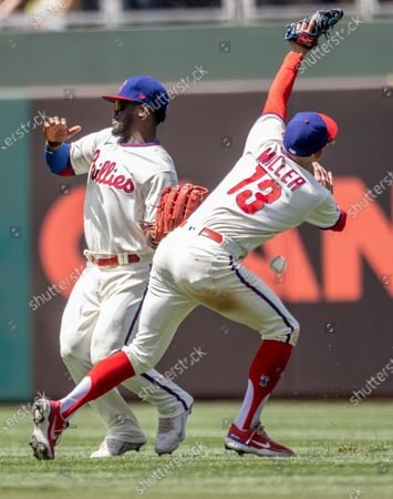 Philadelphia Phillies second baseman Brad Miller, right, and center fielder Odubel Herrera, left, miss a ball hit by Washington Nationals' Victor Robles during the fifth inning of a baseball game, in Philadelphia