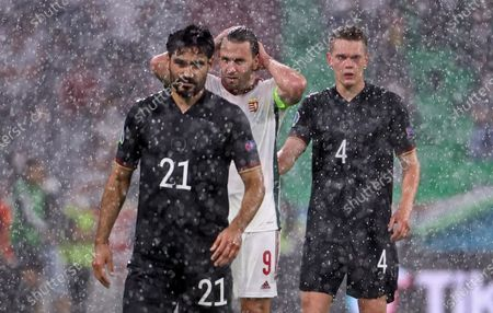 Germany's Ilkay Gundogan, Hungary's Adam Szalai and Germany's Matthias Ginter, from left, stand in the rain during the Euro 2020 soccer championship group F match between Germany and Hungary in Munich