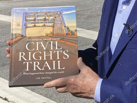 """Lee Sentell, author of """"The Official United States Civil Rights Trail"""" companion book, poses with the book outside the birth home of the Rev. Martin Luther King Jr. in Atlanta on . The U.S. Civil Rights Trail includes more than 120 sites - churches, schools, courthouses, museums - across 15 states, mostly in the South. The new companion book includes more than 200 images of those landmarks today, as well as photographs from the civil rights era"""