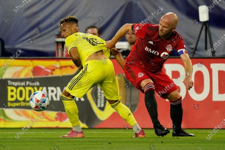 Nashville SC's Hany Mukhtar (10) and Toronto FC's Michael Bradley (4) vie for the ball during the first half of an MLS soccer match, in Nashville, Tenn