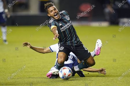 Los Angeles Galaxy midfielder Jonathan dos Santos (8) falls as Vancouver Whitecaps midfielder Caio Alexandre, rear, goes after the ball in the second half during an MLS soccer match, in Sandy, Utah