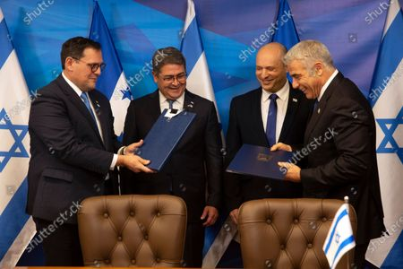 Israeli Prime Minister Naftali Bennett, second right, and Honduran President Juan Orlando Hernandez, second left, look on as Israeli Foreign Minister Yair Lapid, right, and Honduran Foreign Minister Lisandro Rosales exchange signed agreements between their two countries at the prime minister's office, in Jerusalem