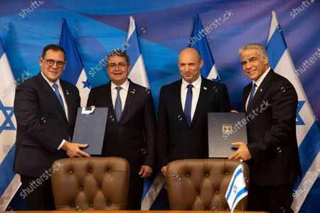 Israeli Prime Minister Naftali Bennett, second right, and Honduran President Juan Orlando Hernandez, second left, look on as Israeli Foreign Minister Yair Lapid, right, and Honduran Foreign Minister Lisandro Rosales hold signed agreements between their two countries at the prime minister's office, in Jerusalem