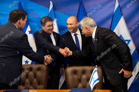 Israeli Prime Minister Naftali Bennett, second right, shakes hands with Honduran Foreign Minister Lisandro Rosales as Honduran President Juan Orlando Hernandez, second left, shakes hands with Israeli Foreign Minister Yair Lapid, after signing agreements between their two countries, at the prime minister's office, in Jerusalem